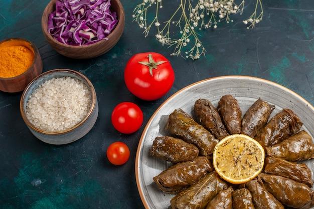 Dolma de folha de frente, deliciosa refeição de carne oriental enrolada em folhas verdes com tomates e temperos na mesa azul