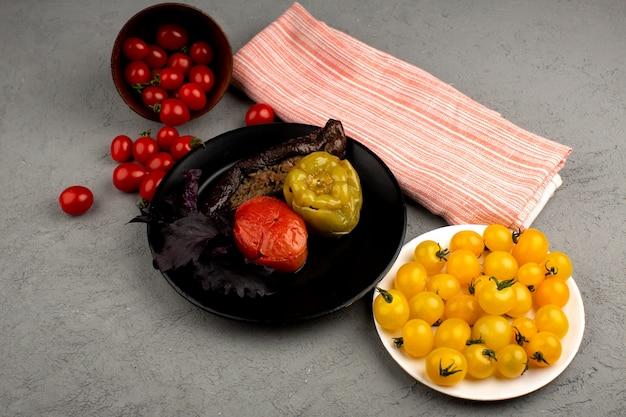 Dolma famoso prato de carne oriental dentro de chapa preta, juntamente com tomates vermelhos e amarelos no chão brilhante