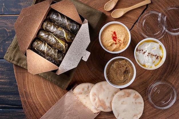 Dolma, sarma ou dolmades turcos. prato tradicional do mediterrâneo dolmadakia ou tolma. folhas de uva recheadas. embalagem para entrega