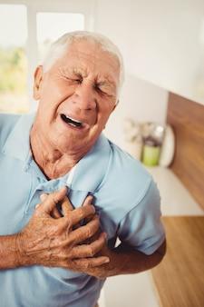 Doloroso homem sênior com dor no coração em casa