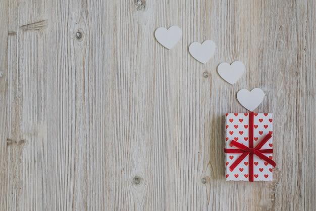 Dom de bolinhas com a curva vermelha com corações de papel em uma mesa de madeira