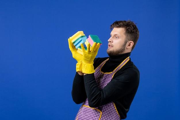 Doméstico de frente segurando esponjas de prato no espaço azul
