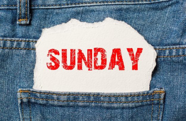 Domingo em papel branco no bolso da calça jeans azul