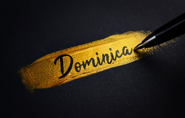 Dominica handwriting text on golden pincelada de pincel