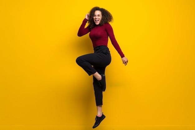 Dominicana mulher com cabelo encaracolado pulando na parede amarela