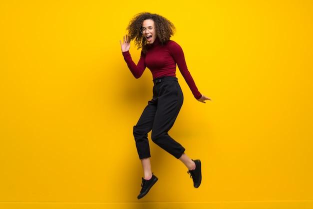 Dominicana mulher com cabelos cacheados, saltando sobre parede amarela isolada