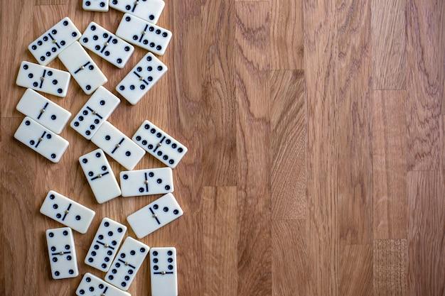 Dominó branco na mesa de madeira, vista de cima, jogo de tabuleiro para texto