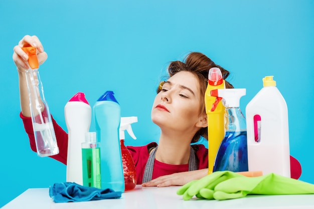 Dona de casa agradável verifica informações na garrafa e posa com coisas de limpeza