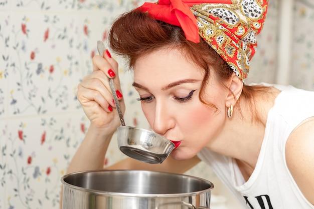 Dona de casa alegre em um lenço vermelho na cozinha tenta a sopa