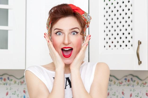 Dona de casa alegre em um lenço vermelho na cozinha