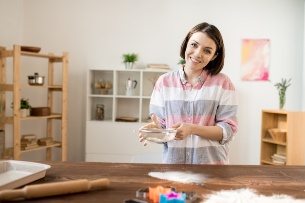 Dona de casa alegre nova que peneira a farinha pela peneira sobre a mesa de madeira ao preparar a massa para a pastelaria caseira