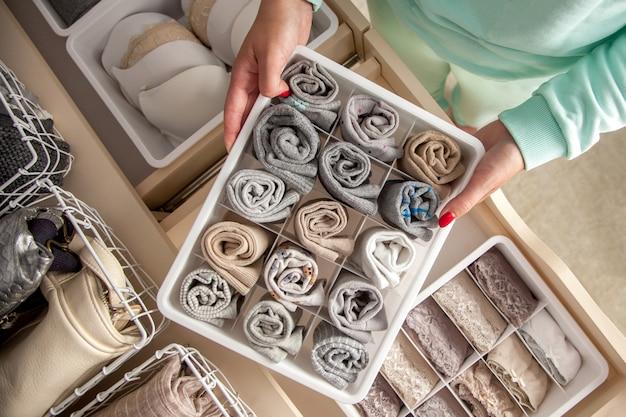 Dona de casa arrumada não identificada coloca recipiente com meias, calcinhas e cuecas. armazenamento de roupas.