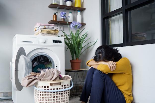 Dona de casa asiática bonita estressada lavando roupa em casa
