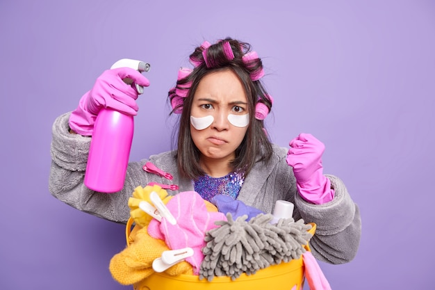 Dona de casa asiática indignada fecha os punhos estando zangada com alguém aperta o punho segura frasco de detergente aplica manchas sob os olhos bobes de cabelo poses perto de uma bacia de roupas sujas isolada na parede roxa