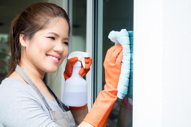 Dona de casa asiática limpando vidro de janela