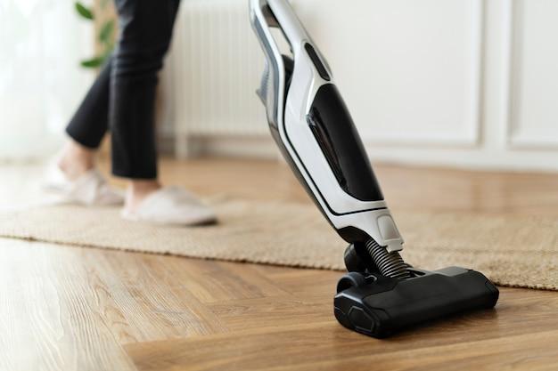 Dona de casa aspirando piso de parquete