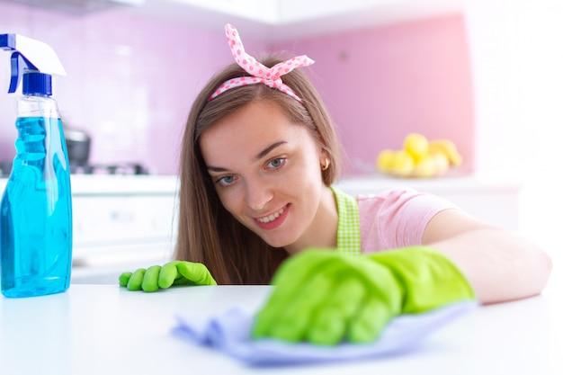 Dona de casa atraente jovem em luvas de borracha protetora, limpando a poeira de móveis na cozinha em casa, usando um pano e spray. limpeza e arrumação de primavera