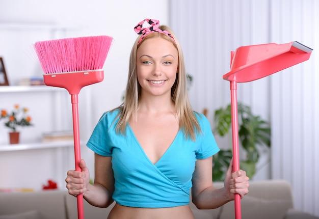 Dona de casa bonita com uma vassoura para limpar em casa.