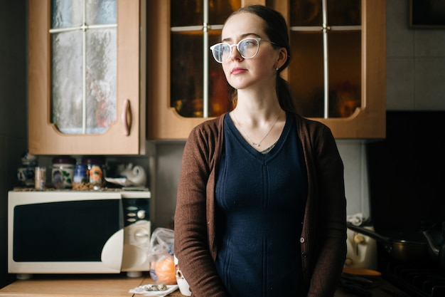 Dona de casa bonita nova nos vidros que levanta na cozinha