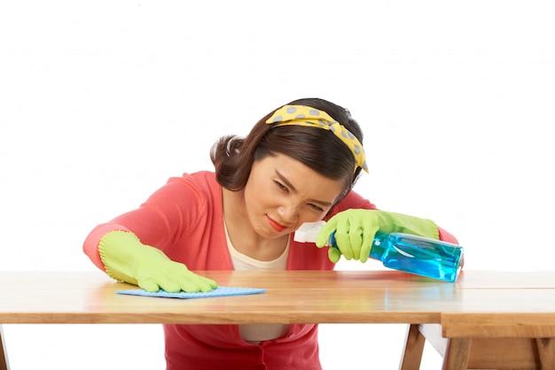 Dona de casa bonita polir a superfície da mesa