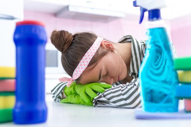 Dona de casa cansada e sobrecarregada que descansa durante a limpeza da primavera na cozinha em casa. fadiga de limpeza