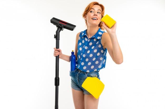 Dona de casa caucasiana com produtos de limpeza e um aspirador de pó nas mãos em uma parede branca