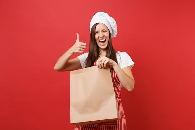 Dona de casa chef feminina cozinheira padeiro em avental listrado camiseta toque chapéu de chef isolado no fundo da parede vermelha mulher segura na mão marrom claro vazio ofício em branco saco de papel para viagem mock up copy space concept