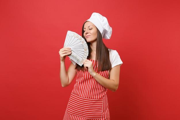 Dona de casa chef feminino cozinheiro padeiro no avental listrado, camiseta branca, chapéu de chefs toque isolado no fundo da parede vermelha. mulher feliz segurando lotes de notas de dólares em dinheiro. mock-se o conceito de espaço de cópia.