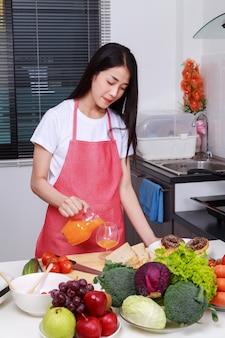 Dona de casa com derramando suco de laranja jar na sala de cozinha
