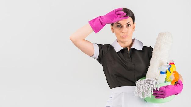 Dona de casa com detergentes esfregando a testa