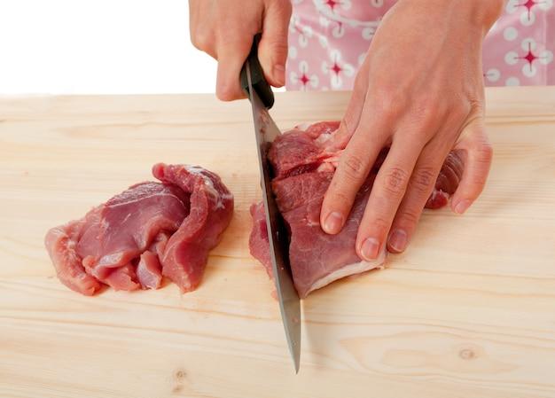 Dona de casa cortando carne em uma placa de madeira.