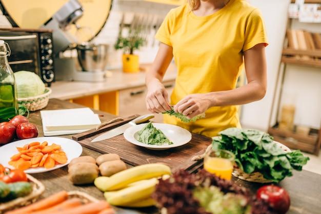 Dona de casa cozinhando na cozinha, comida saudável e biológica. dieta vegetariana, vegetais frescos e frutas na mesa de madeira