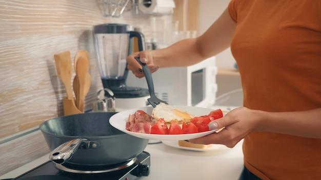 Dona de casa cozinhando ovos no café da manhã na cozinha. manhã saudável com produtos frescos, estilo de vida feliz para a dona de casa que cozinha em uma cozinha moderna e aconchegante sob a luz quente da manhã ensolarada de verão