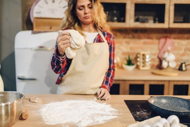 Dona de casa de avental cozinhando massa em tigela de metal