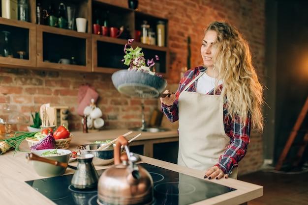 Dona de casa de avental fritando legumes em uma panela