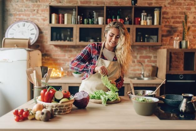 Dona de casa de avental prepara salada na cozinha