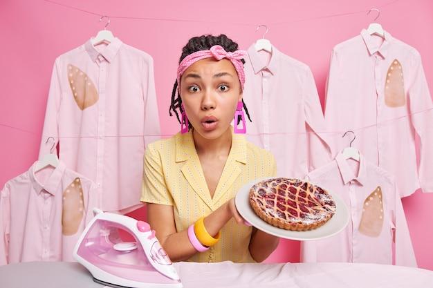 Dona de casa de mulher étnica surpresa segura torta assada apetitosa no prato ocupado passando e cozinhando em casa usa bandana roupas domésticas poses contra camisas queimadas passadas a ferro penduradas na corda.