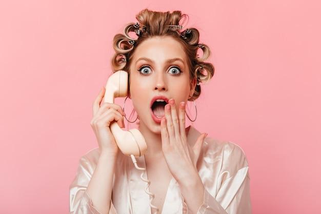 Dona de casa de olhos cinzentos com manto cobrindo a boca de surpresa e falando ao telefone