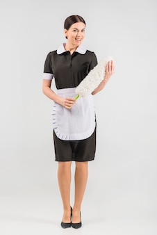 Dona de casa de uniforme com espanador sorrindo