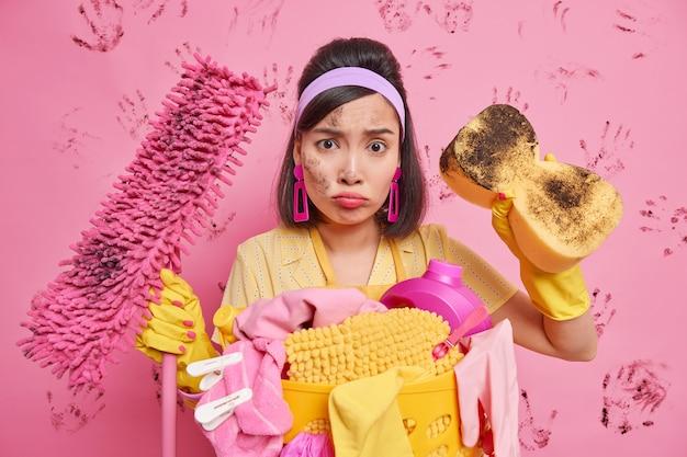 Dona de casa descontente olhando tristemente para a câmera com a cara suja segurando poses de equipamento de limpeza perto do cesto de roupa suja com prendedores de roupa isolados sobre a parede rosa