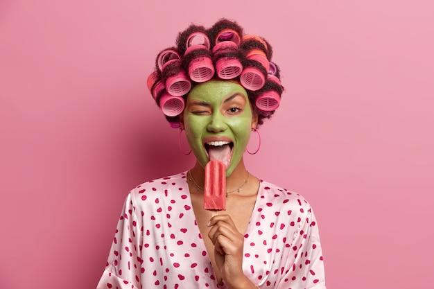 Dona de casa divertida e alegre lambe um delicioso sorvete, pisca os olhos, tem prazer em comer uma sobremesa gelada e refrescante de verão, usa máscara verde no rosto, enroladores de cabelo, vestida com roupa casual, se diverte em casa