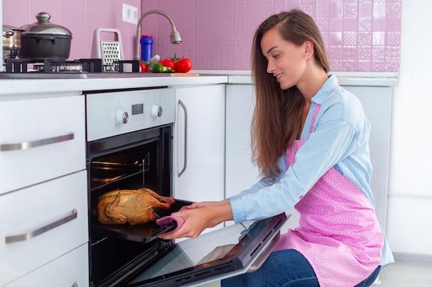Dona de casa em avental assando frango no forno para jantar na cozinha