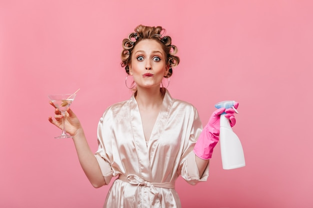 Dona de casa engraçada com bobes de cabelo posando com copo de martini e detergente