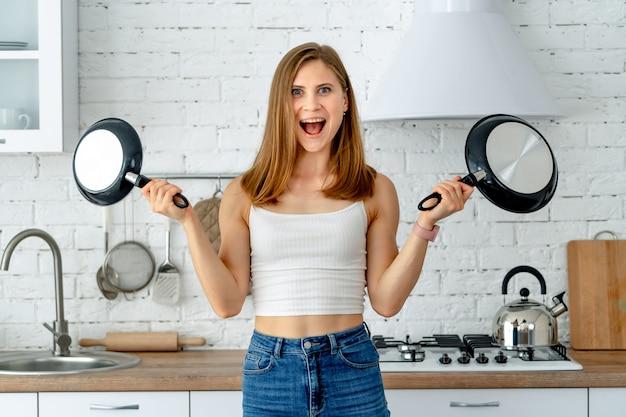 Dona de casa engraçada com utensílios de cozinha