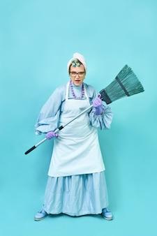 Dona de casa engraçada idosa brincando com uma vassoura