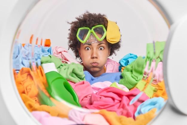 Dona de casa engraçada usa óculos de mergulho, assoa as bochechas faz careta lava roupa em casa carrega máquina de lavar com roupas sujas poses de dentro da máquina de lavar