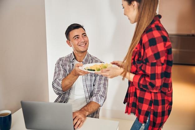 Dona de casa entregando omelete com salada para o marido