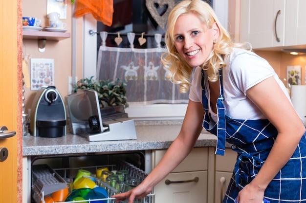 Dona de casa está lavando a louça com máquina de lavar louça