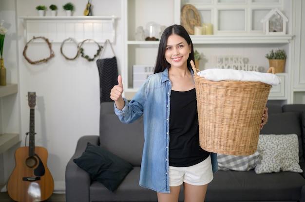 Dona de casa feliz carregando panos de balde para a roupa suja da casa