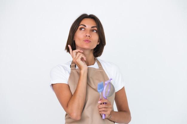 Dona de casa feliz no avental isolado no branco pensativa, pense na receita o que fazer